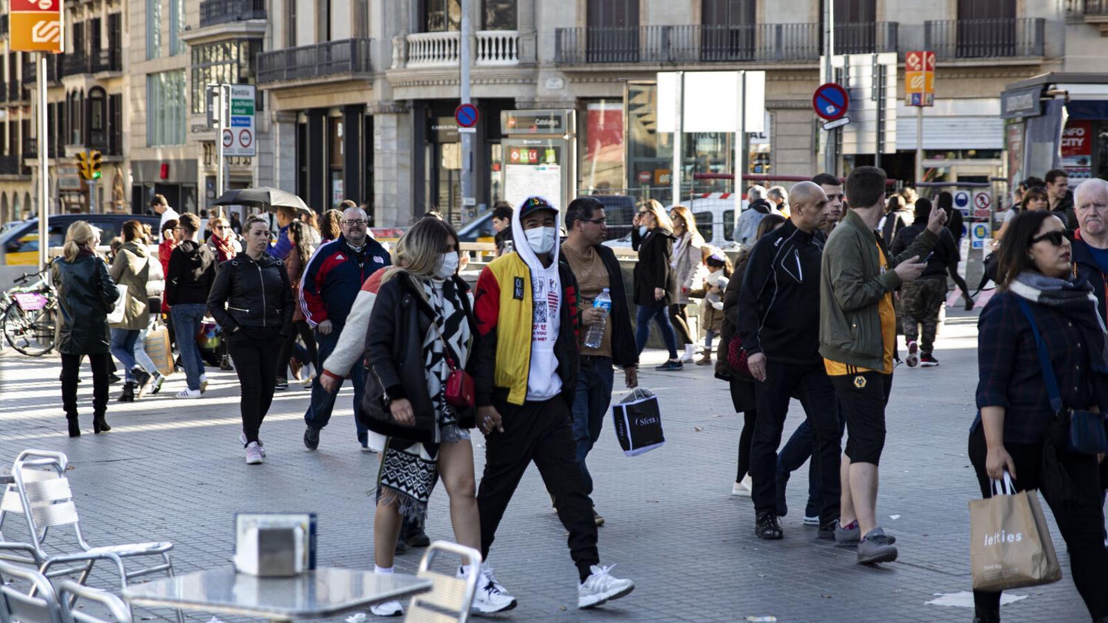 Diverses persones passejant per la plaça Catalunya de Barcelona, en una imatge d'arxiu durant la pandèmia / Sara Cabarrocas