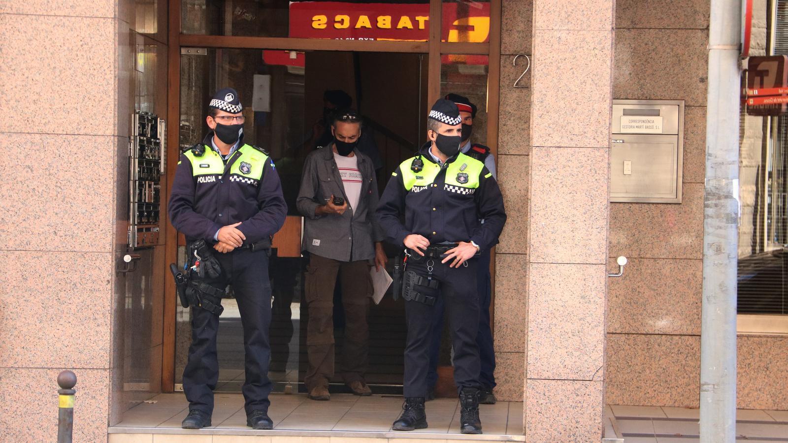 Agents de la Policia Municipal de Girona i dels Mossos a les portes de l'edifici on han trobat la dona