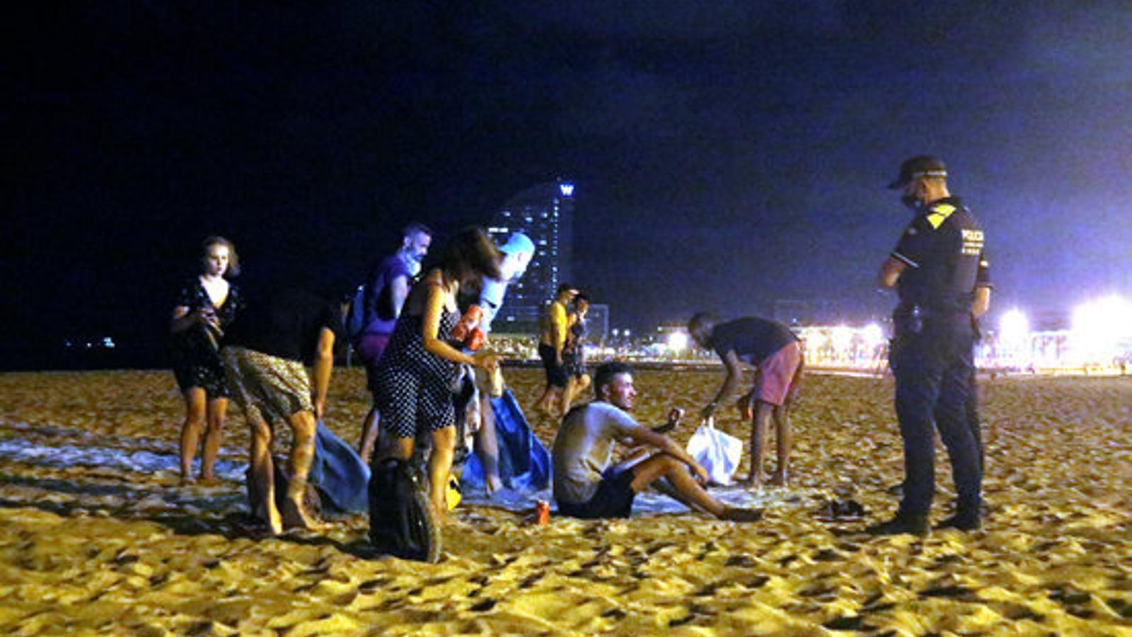 Un grup de persones que feia 'botellón' a la platja a Barcelona s'aixeca després de l'arribada de la Guàrdia Urbana, el passat 29 de juliol, quan va entrar en vigor la prohibició
