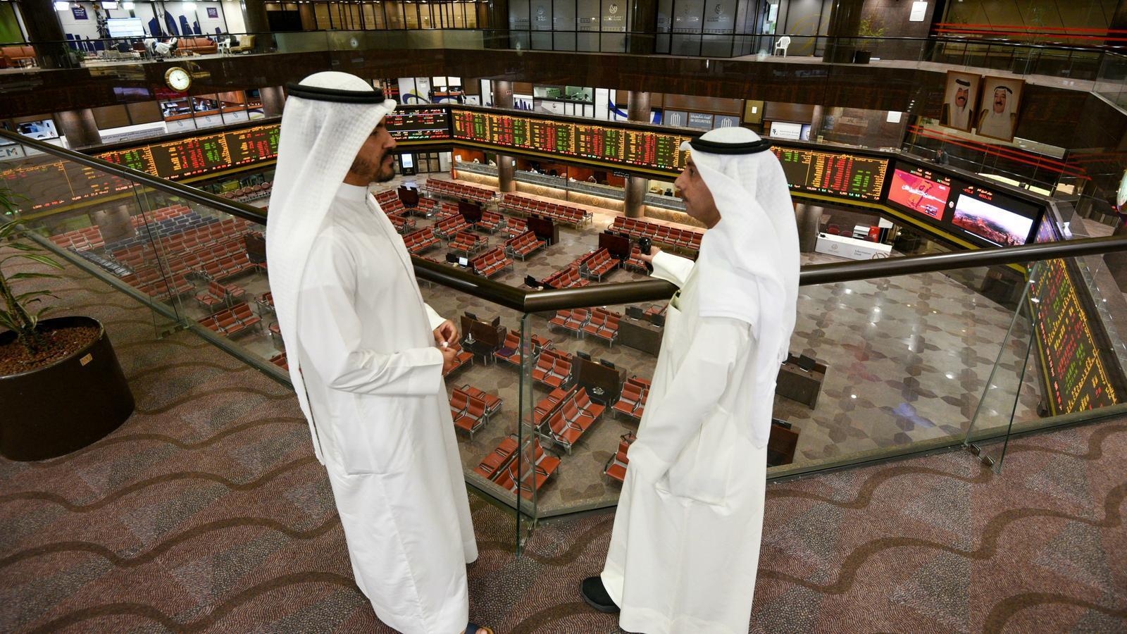 Gent observant el desenvolupament del mercat nacional Boursa Kuwait a Kuwait