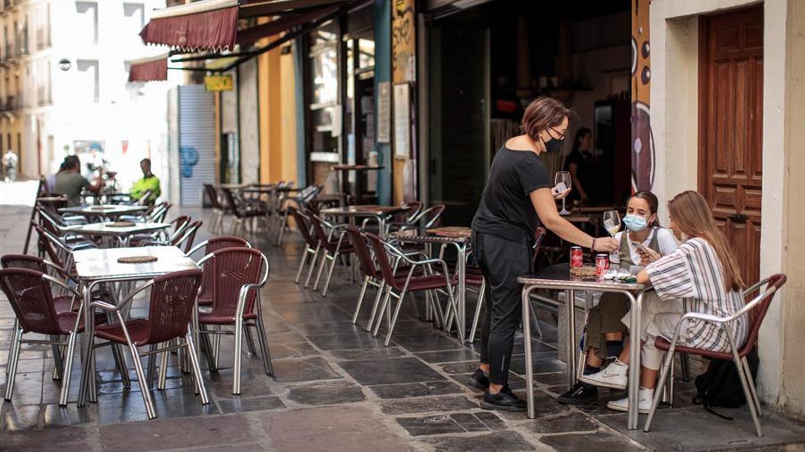 Una cambrera atén una taula d'una terrassa en el centre de València. EFE/Biel Aliño