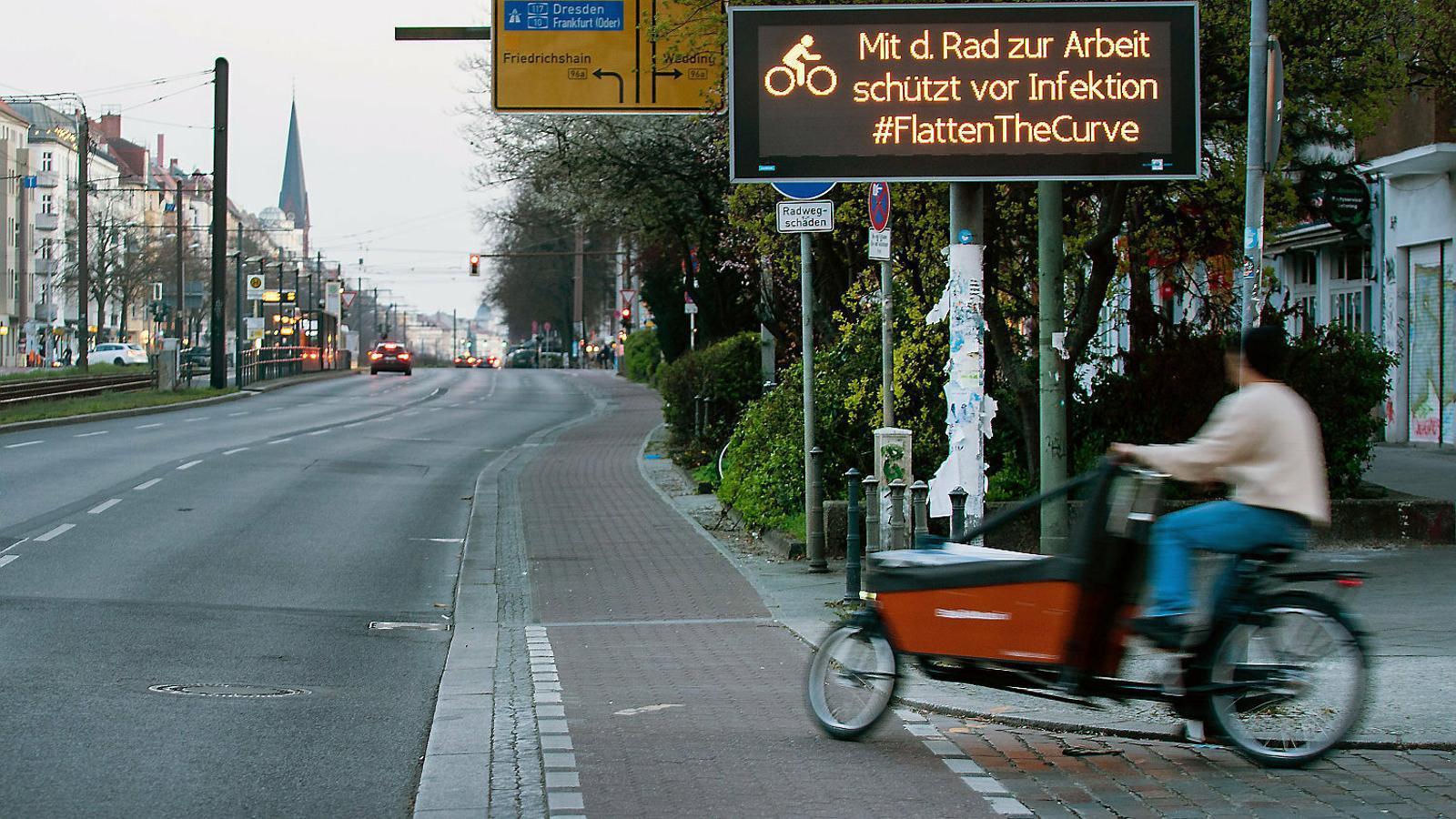 Un home transportant un paquet a Berlín, on un cartell convida els ciutadans a aplanar la corba de contagis pel coronavirus.
