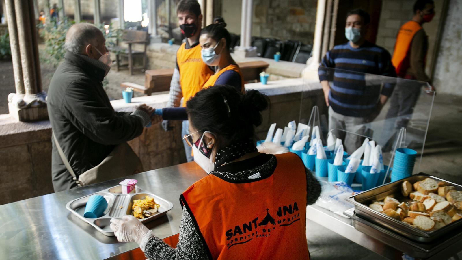 Voluntaris de l'Hospital de Campanya saludant un dels usuaris que arriba per dinar al claustre