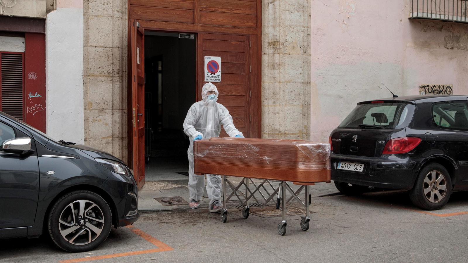 Un treballador sanitari transporta un taüt a les portes del geriàtric Palau de Raga de València