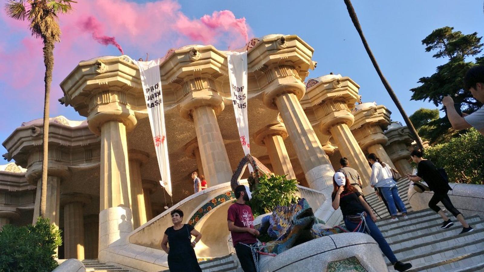 Joves d'Arran s'encadenen al drac del Parc Güell en protesta contra el model turístic