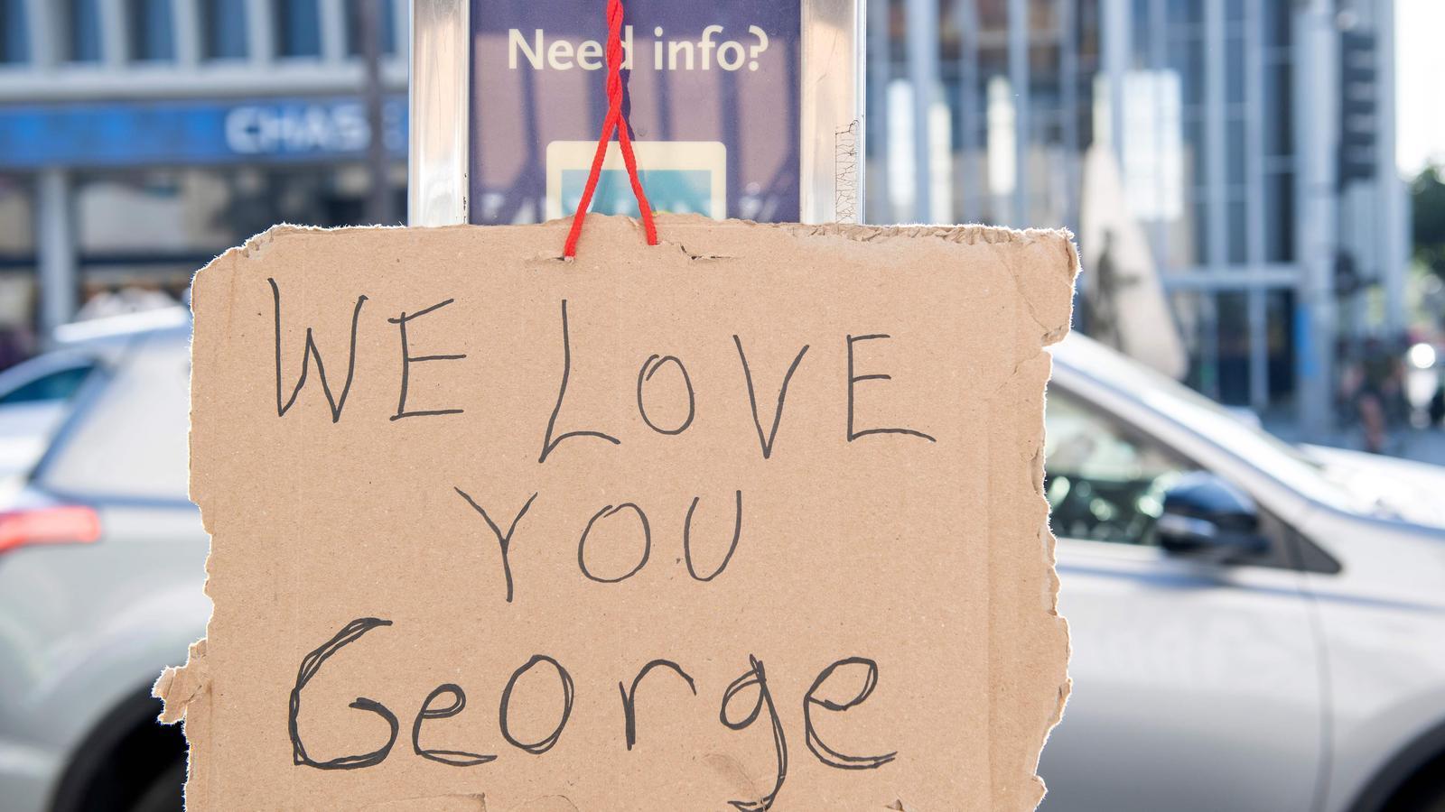 """Un cartell rudimentari amb el missatge """"T'estimem, George"""", penjat en un carrer de Los Ángeles"""
