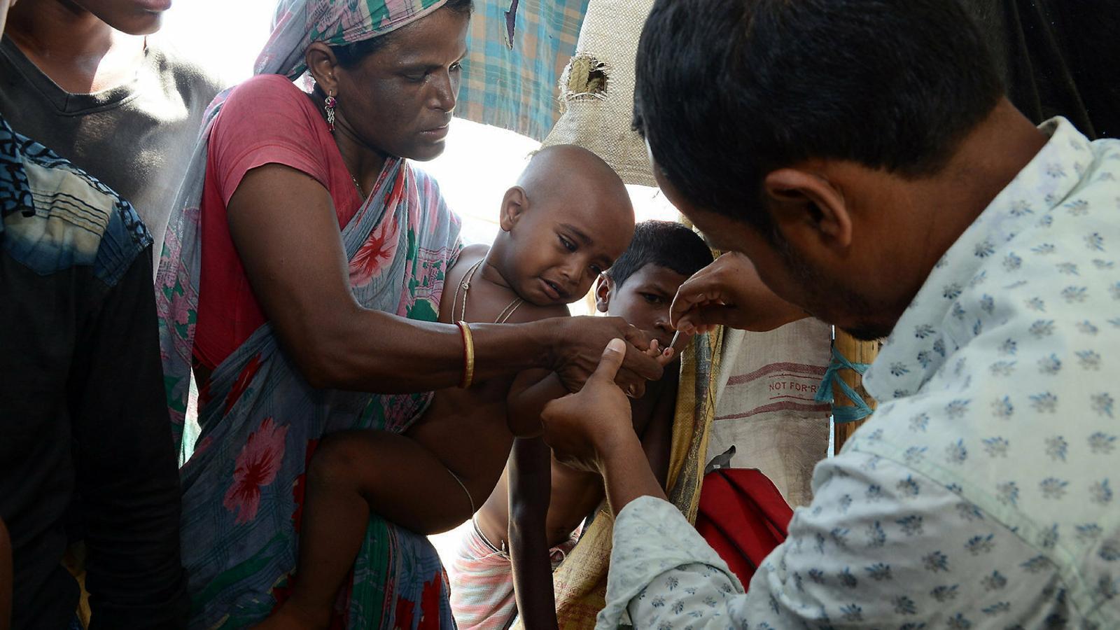 Un metge fent una prova de sang a un nen en una ciutat de l'Índia per comprovar si té la malària.