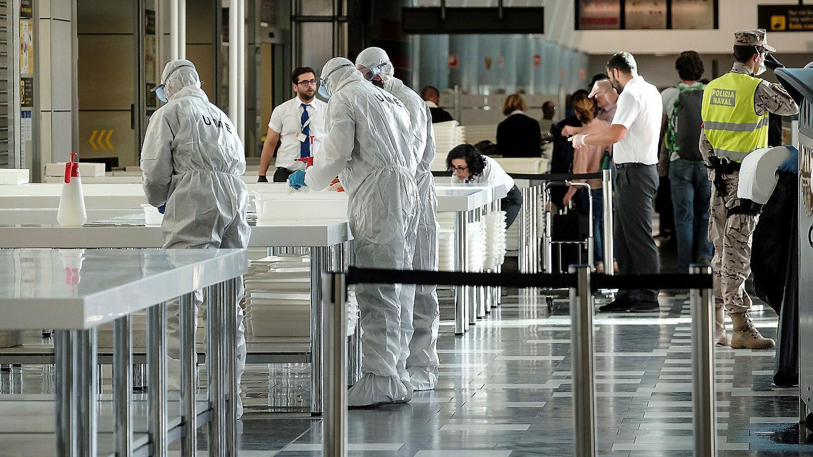 Membres de la Unitat Militar d'Emergència desinfectant divendres una de les zones d'embarcament de l'aeroport de Gran Canària .