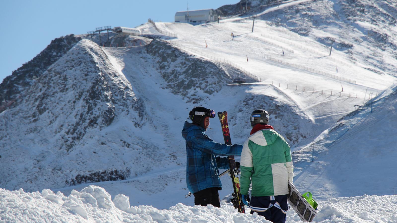 Dos joves es preparen per esquiar al Pas de la Casa.