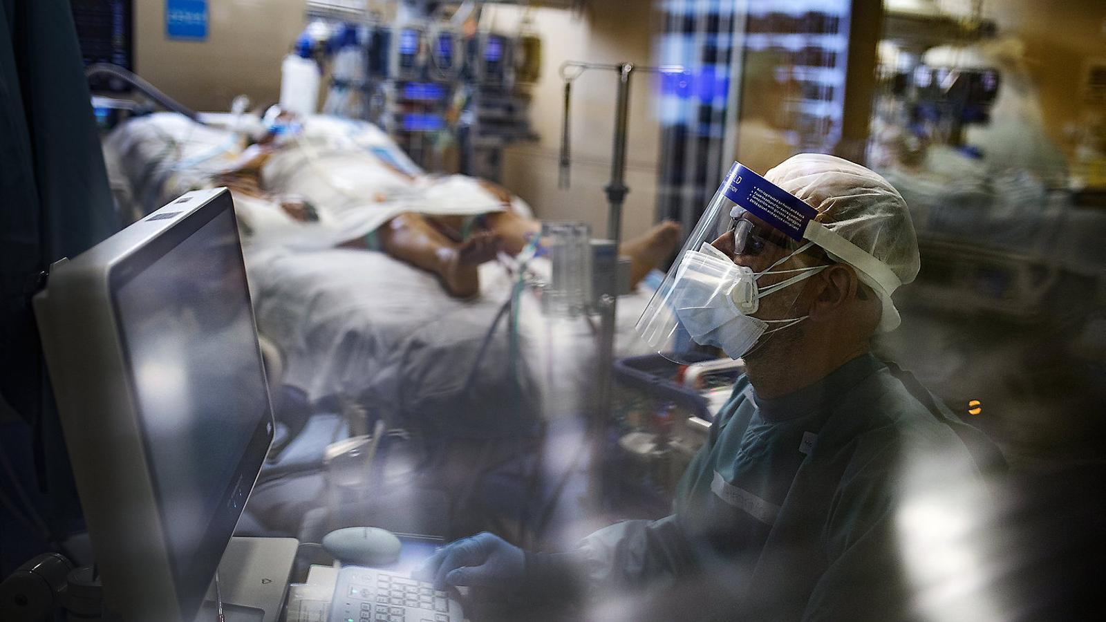 Un sanitari de l'Hospital de la Vall d'Hebron monitoritzant un malalt de covid-19 a l'UCI.