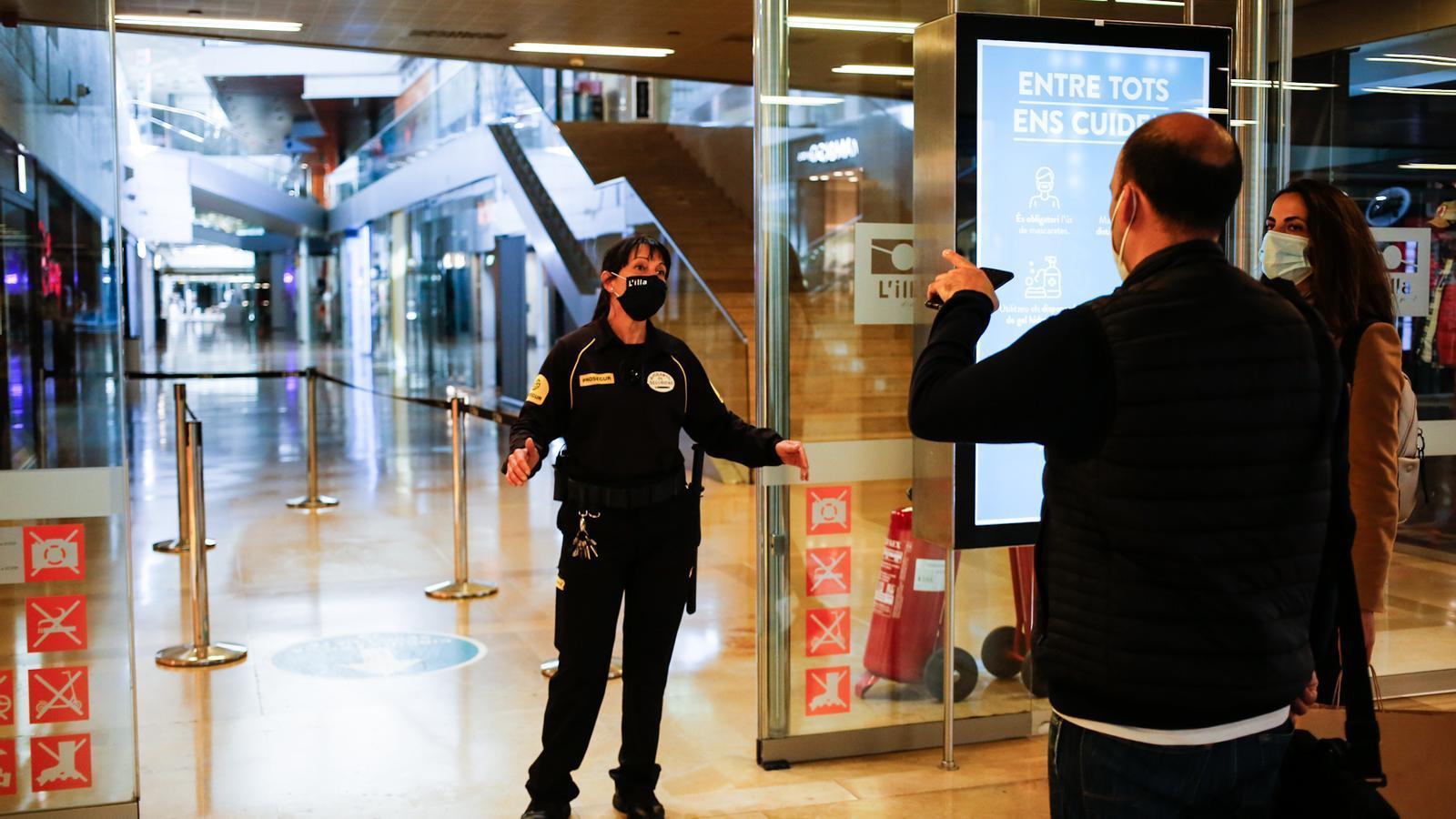 Una vigilant de seguretat avisa els compradors a l'entrada del centre comercial L'Illa.