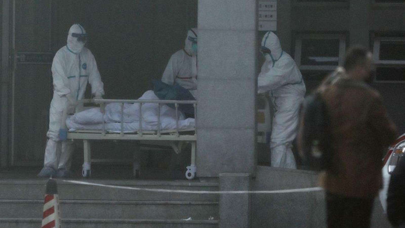 Un grup de sanitaris traslladen una persona contagiada per la pneumònia de Wuhan.