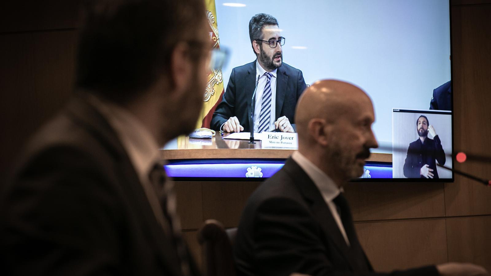 El ministre portaveu, Eric Jover, reflectit a la plantalla televisiva de la sala on es fan les rodes de premsa del Govern. / SFG