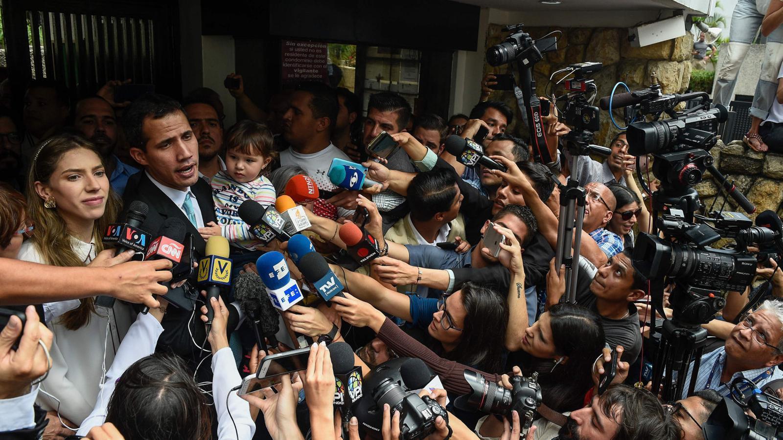 El proclamat president interí de Veneçuela, Juan Guaidó, atén la premsa amb la seva dona i la seva filla d'un any.