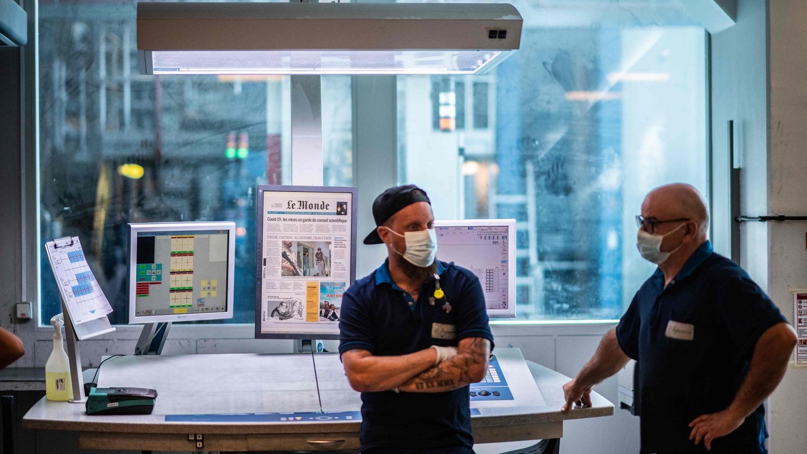 Dos treballadors amb mascareta en la impremta de París on s'imprimeix el diari francès Le Monde