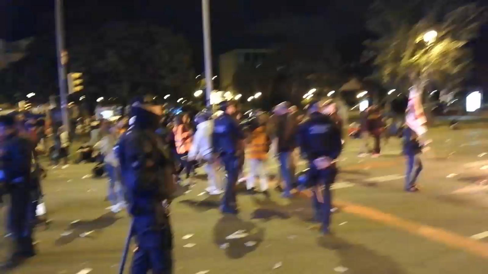 Els mossos demanen als manifestants que queden que s'enretirin perquè els bombers puguin apagar la foguera