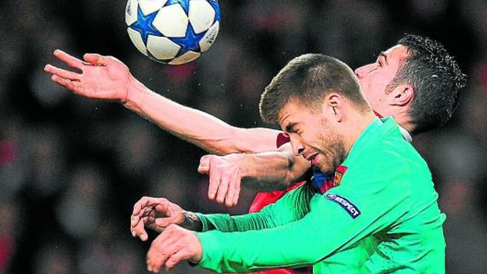 Gerard Piqué salta amb Van Persie per una pilota. / LLUÍS GENÉ / AFP