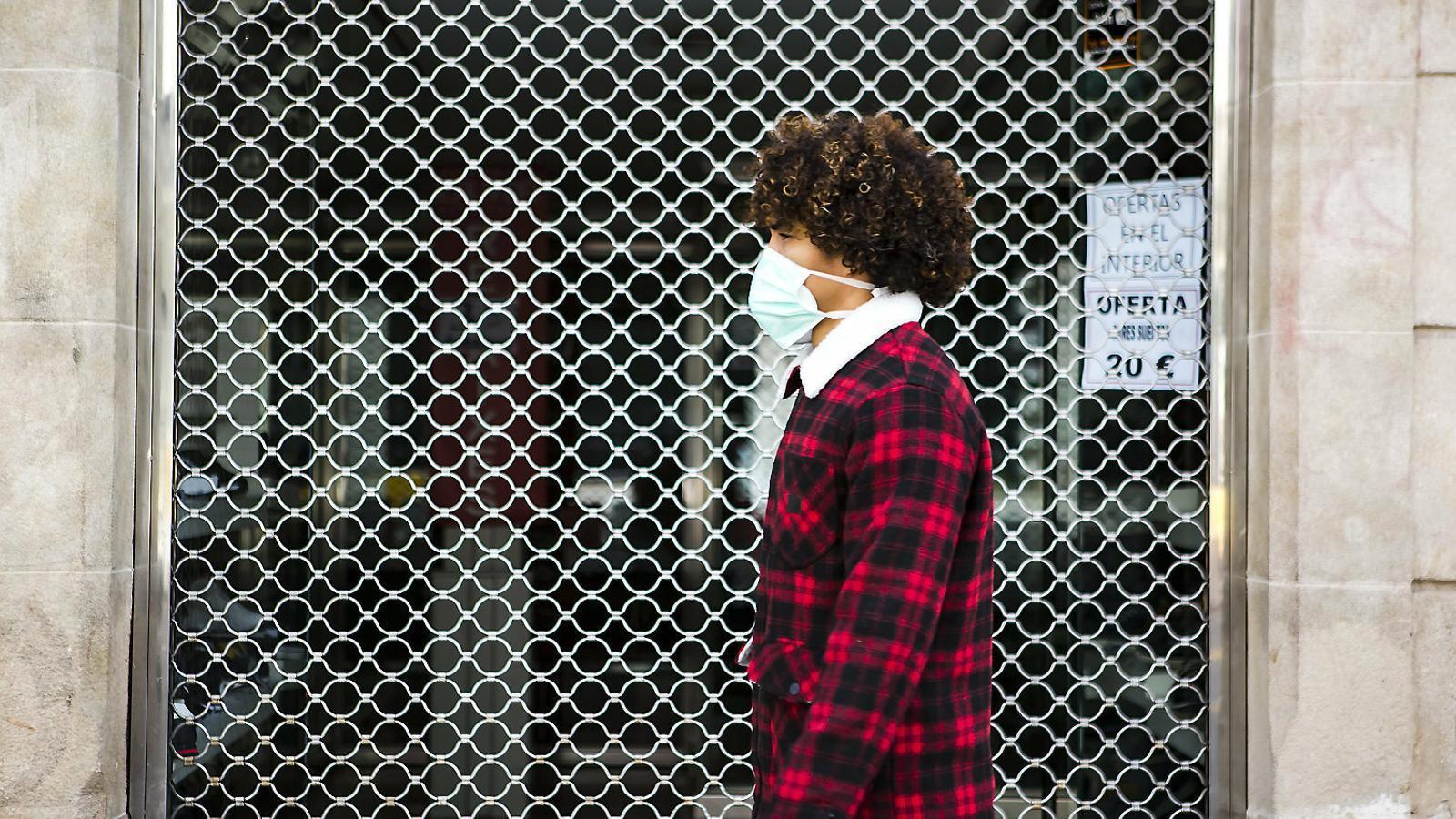 Un noi amb mascareta passant davant una botiga tancada de Barcelona.