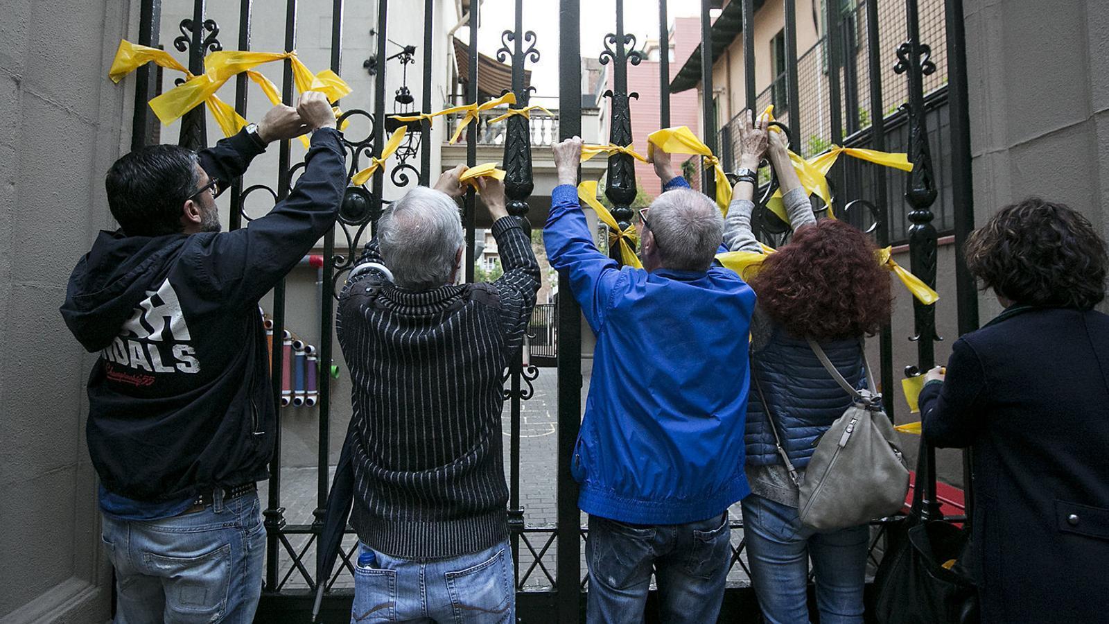 Persones posant llaços a la ciutat de Barcelona en record dels presos i exiliats.