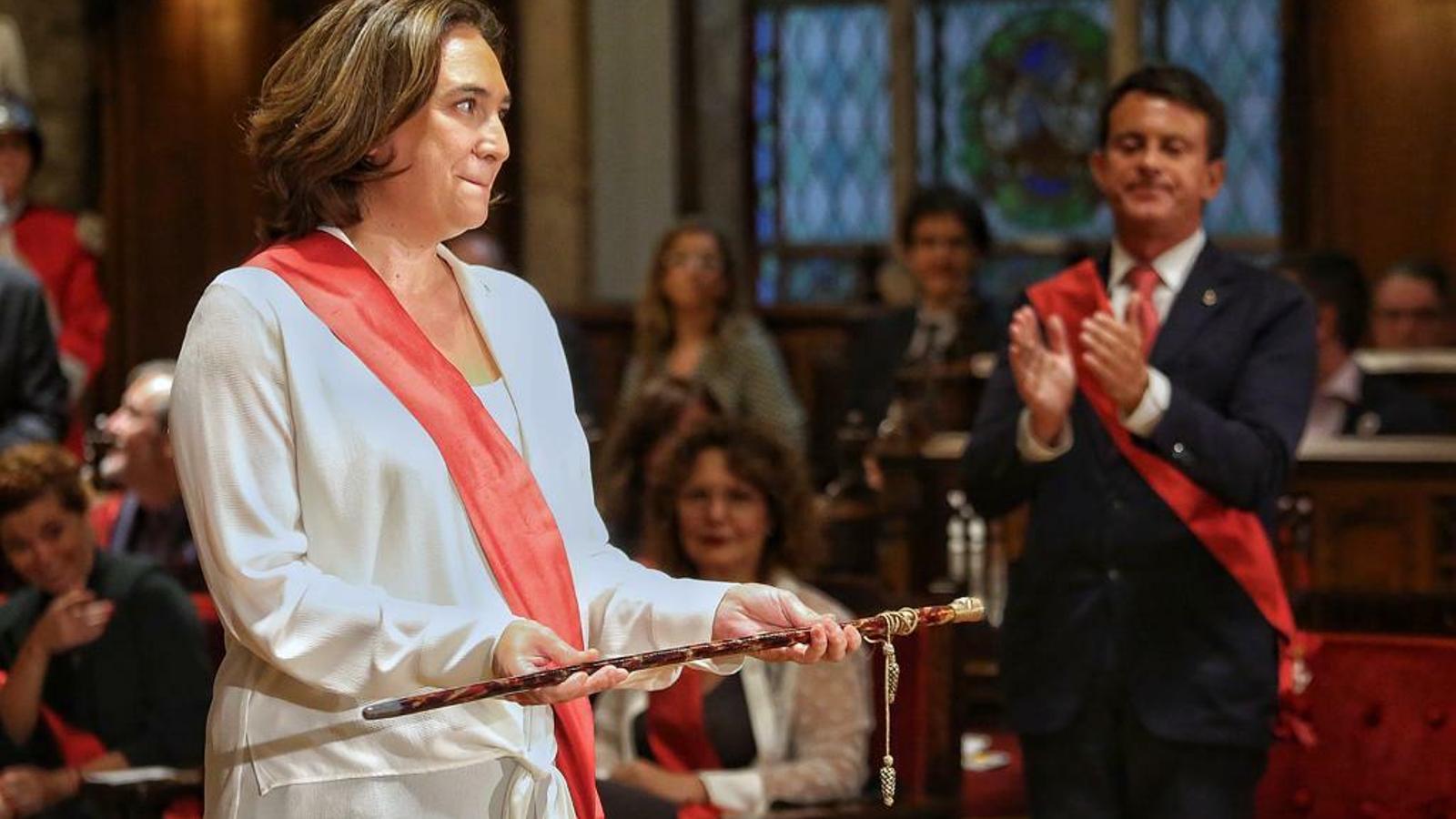Ada Colau sosté la vara d'alcaldessa mentre Manuel Valls l'aplaudeix al fons