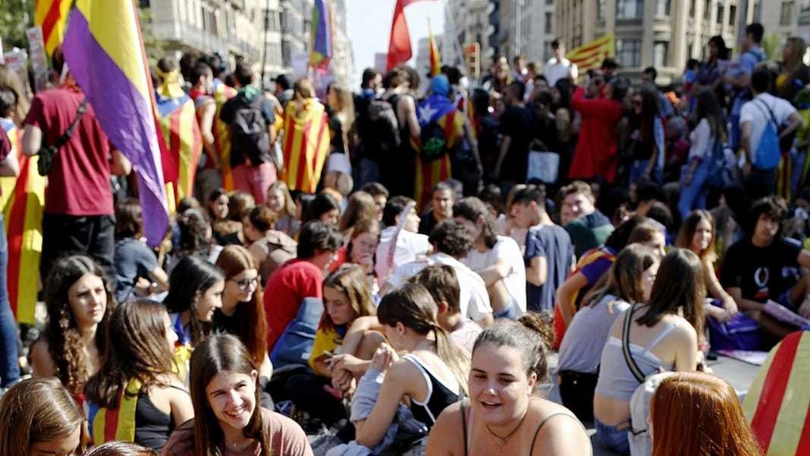 Una manifestant amb una estelada fa un petó a una altra amb una bandera espanyola a la concentració de la plaça Universitat