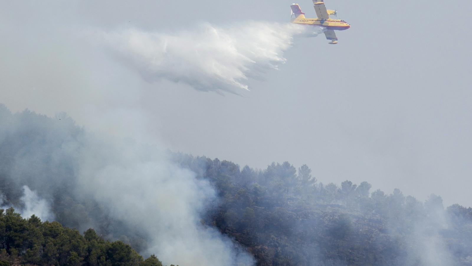 Un dels 27 mitjans aeris que treballen per sufocar l'incendi originat al terme castellonenc d'Artana, realitza una descàrrega a prop del parc natural de la serra d'Espadà.