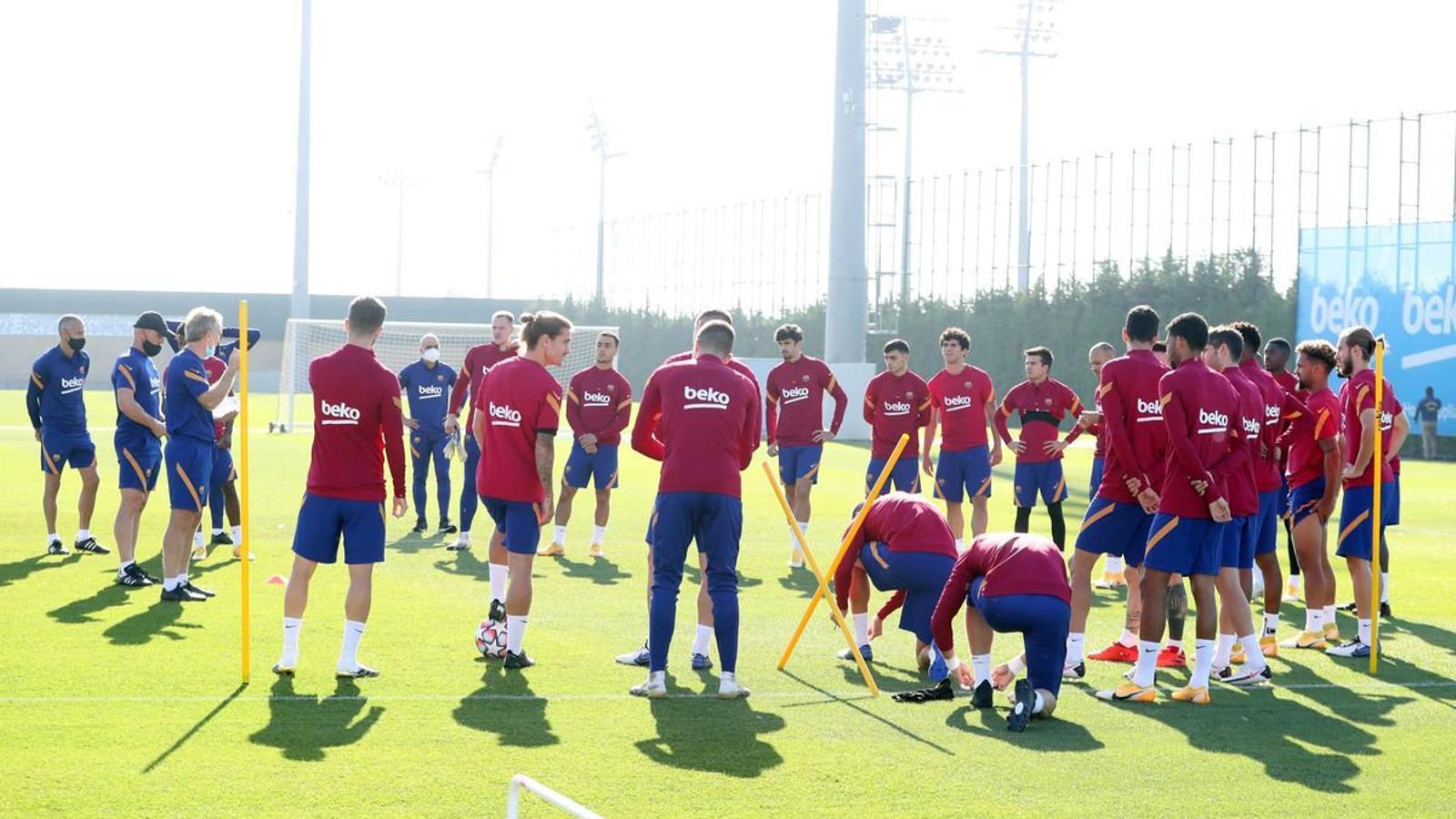 Els jugadors del Barça escoltant les indicacions del cos tècnic durant un entrenament.