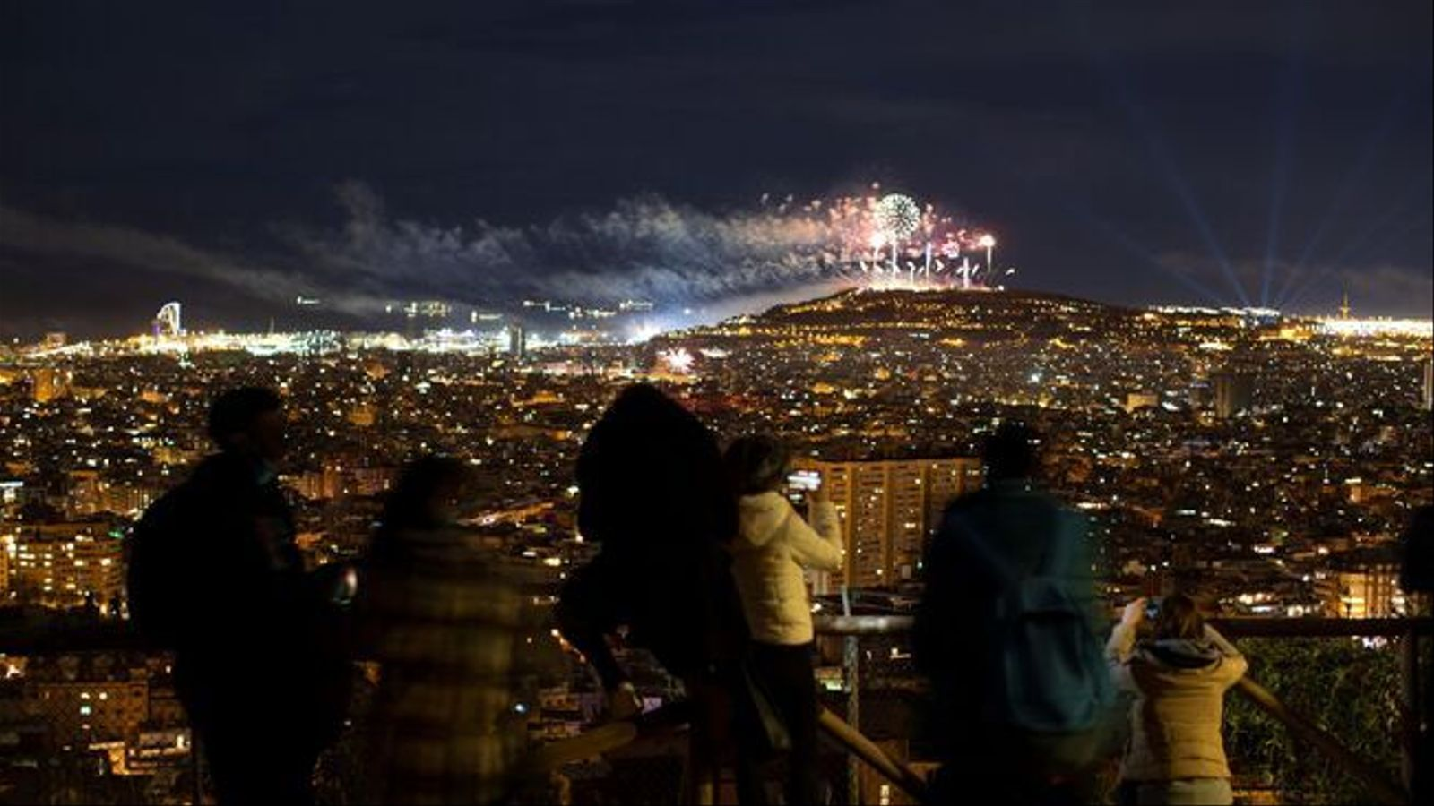 Several people watching the New Year's Eve fireworks in Barcelona