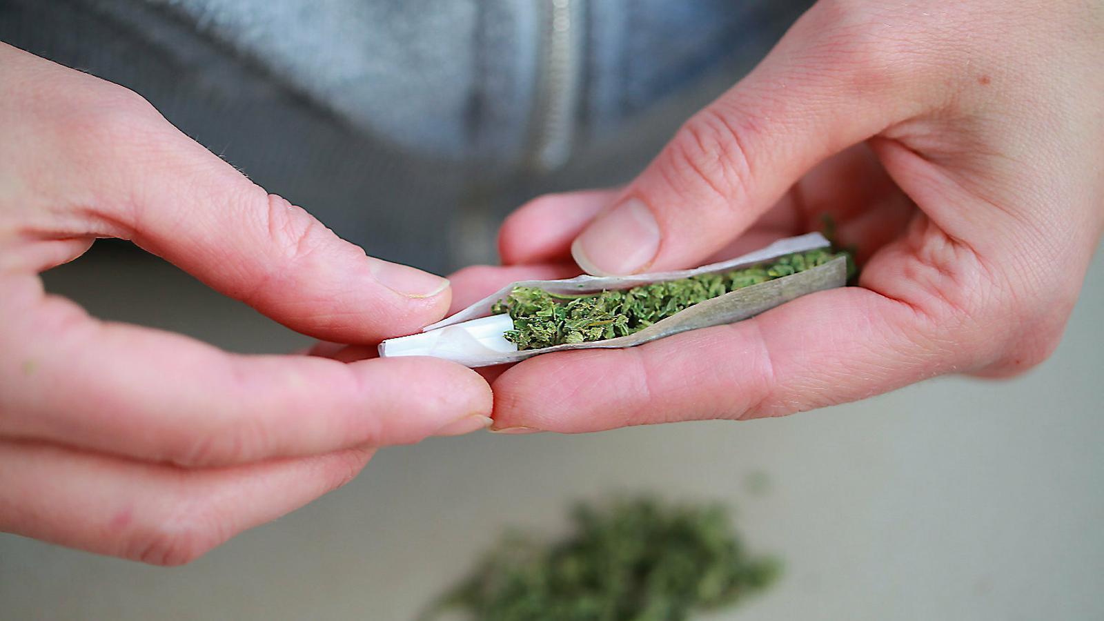 Una persona cargolant un porro de marihuana en una imatge de recurs.
