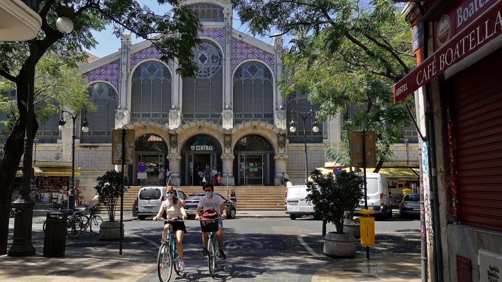 Dues persones passegen amb bicicleta per davant del Mercat Central