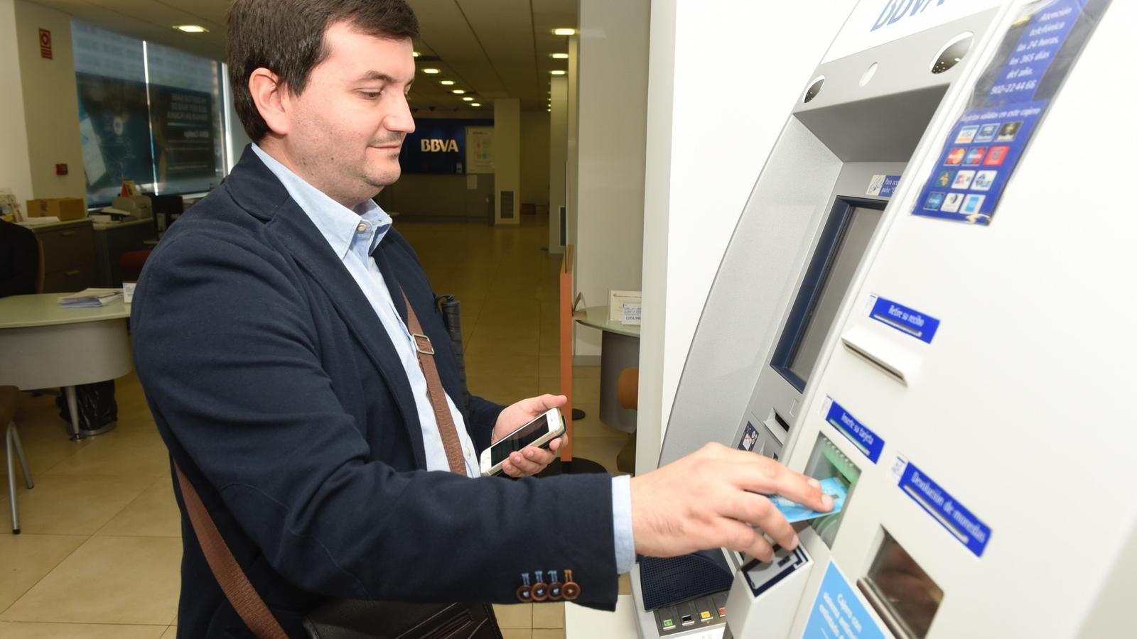 Un usuari de la nova app de BBVA en un caixer automàtic de l'entitat / BBVA