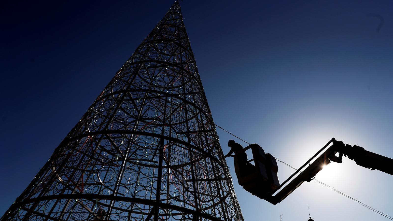Un operari treballa en el muntatge de l'arbre de Nadal a la plaça de l'Ajuntament a València.