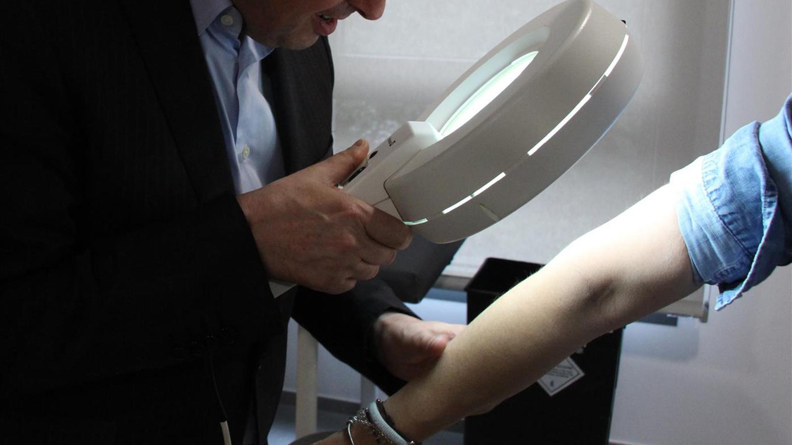 Un dermatòleg controlant la piga d'un pacient. / M.F. (ANA)