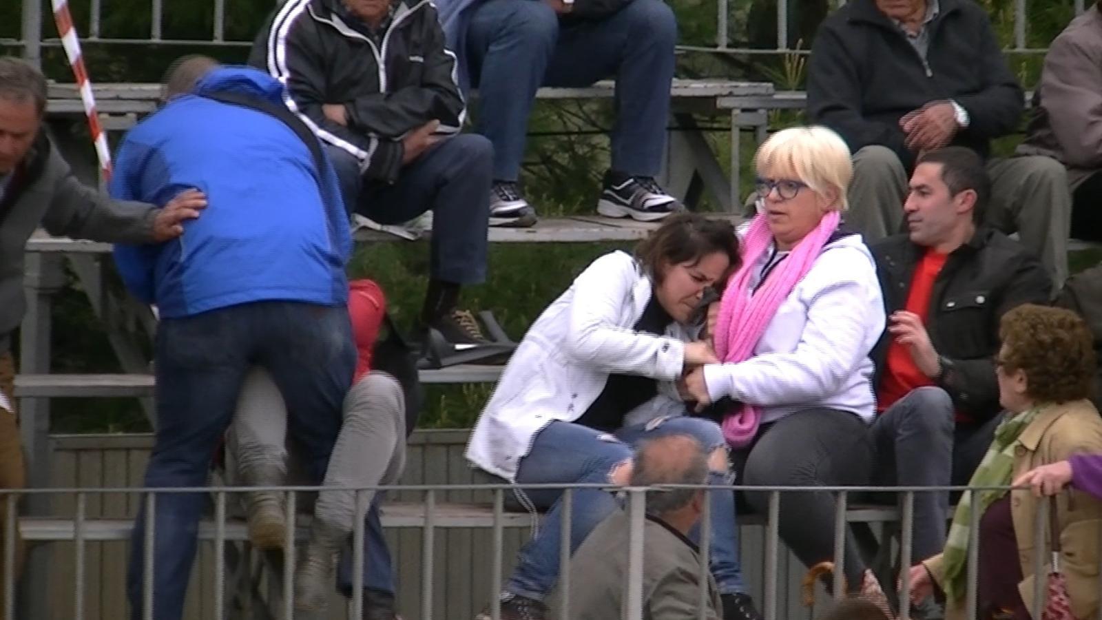 Un home s'abalança sobre una activista mentre una dona intenta treure la càmera a l'altre