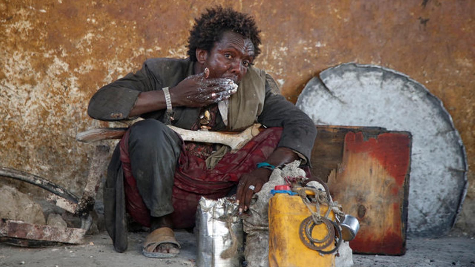 Un home menja unes farinetes al camp de desplaçats de Sorrdo, a Mogadiscio, la capital somali.