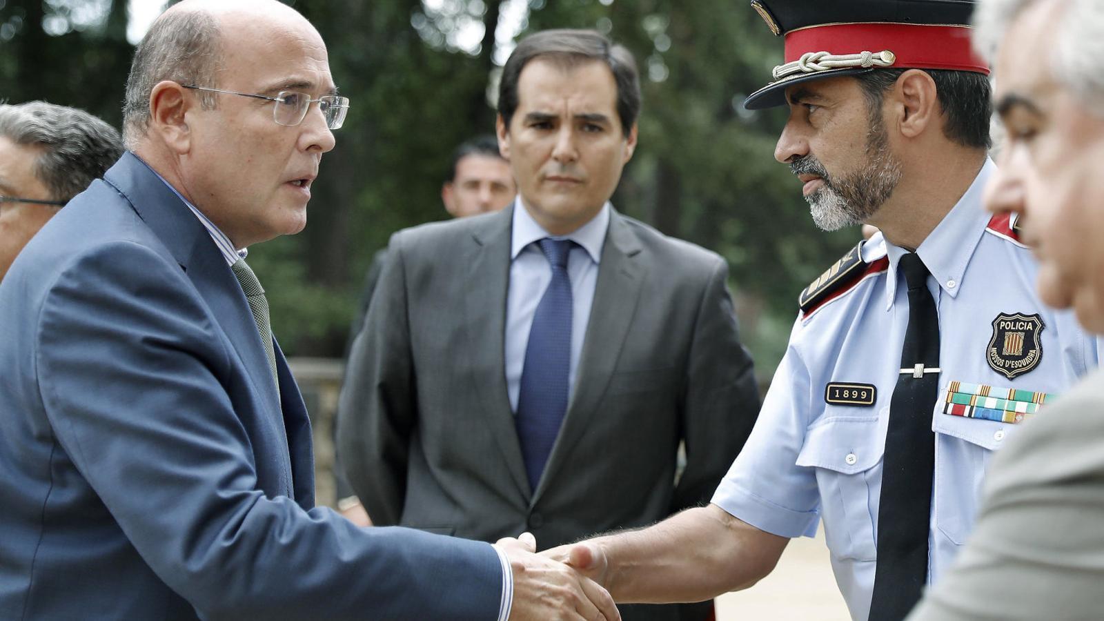 Diego de los Cobos saludant el major Josep Lluís Trapero sota l'atenta mirada de José Antonio Nieto.