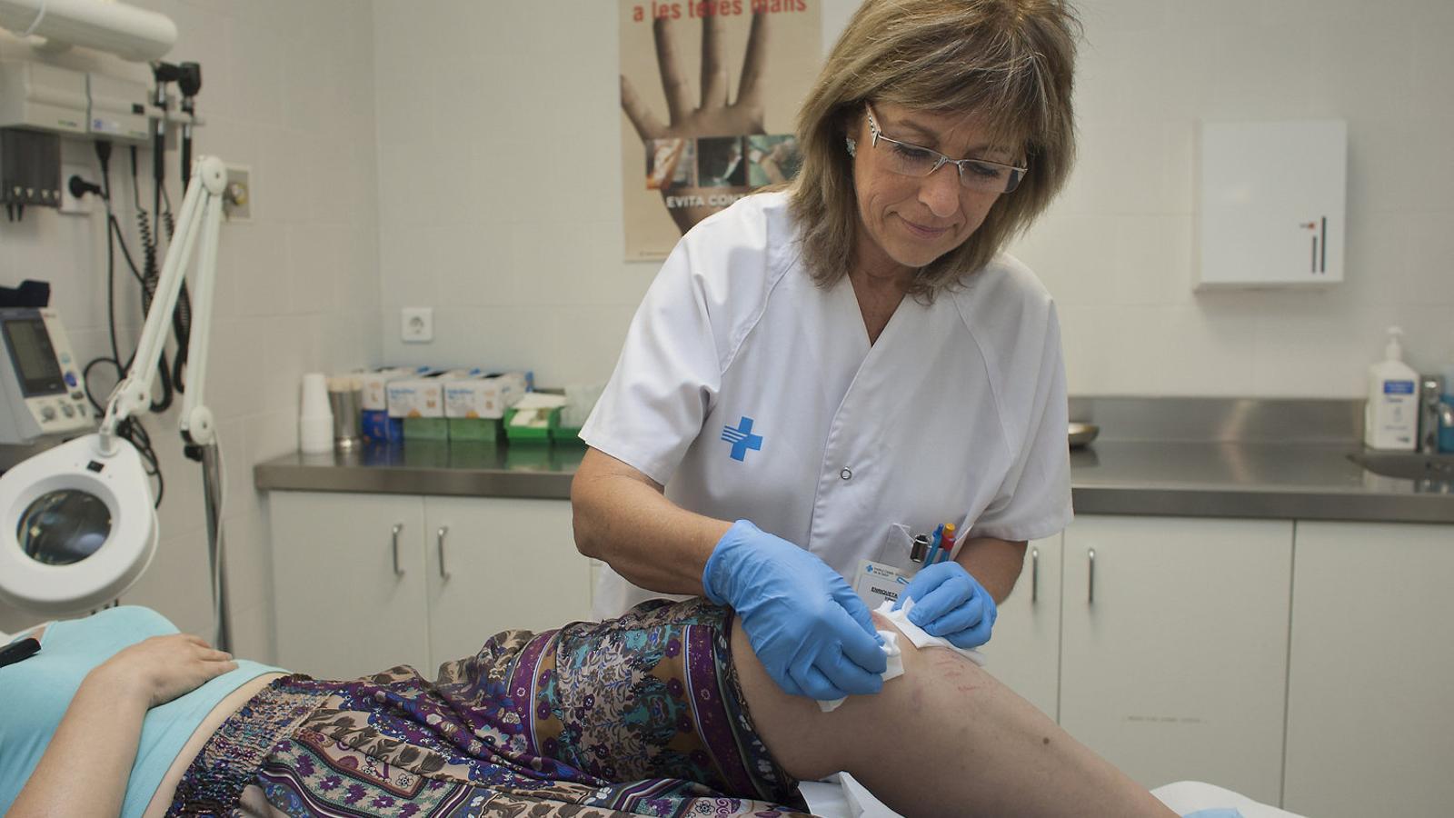 Una infermera practicant una cura a una pacient en  un CAP. / TJERK VAN DER MEULEN