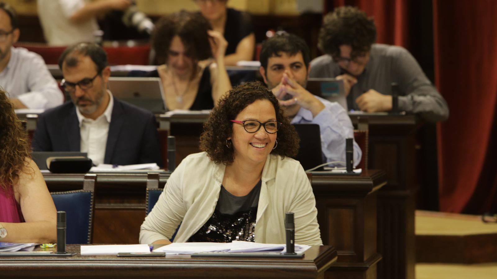 La consellera d'Hisenda, Catalina Cladera, riu escoltant el diputat del PP Antoni Camps.