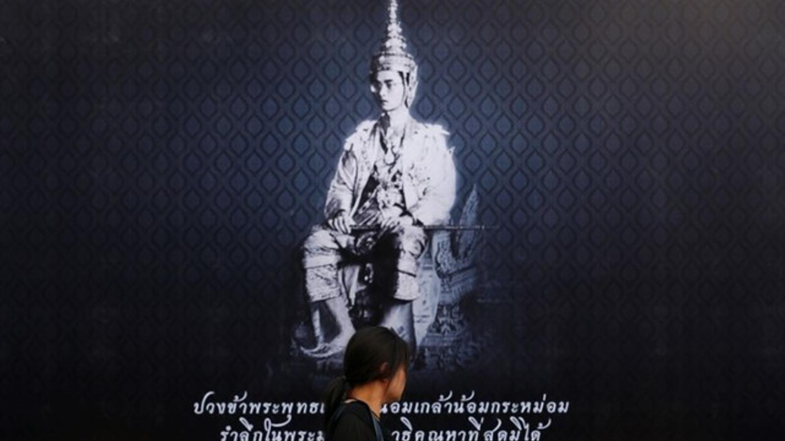 Una dona passa per un cartell que anuncia la mort i el dol pel monarca mort, a Bangkok.