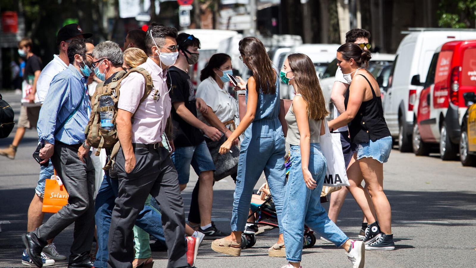 Ciutadans passejant per Barcelona, la majoria amb mascareta.