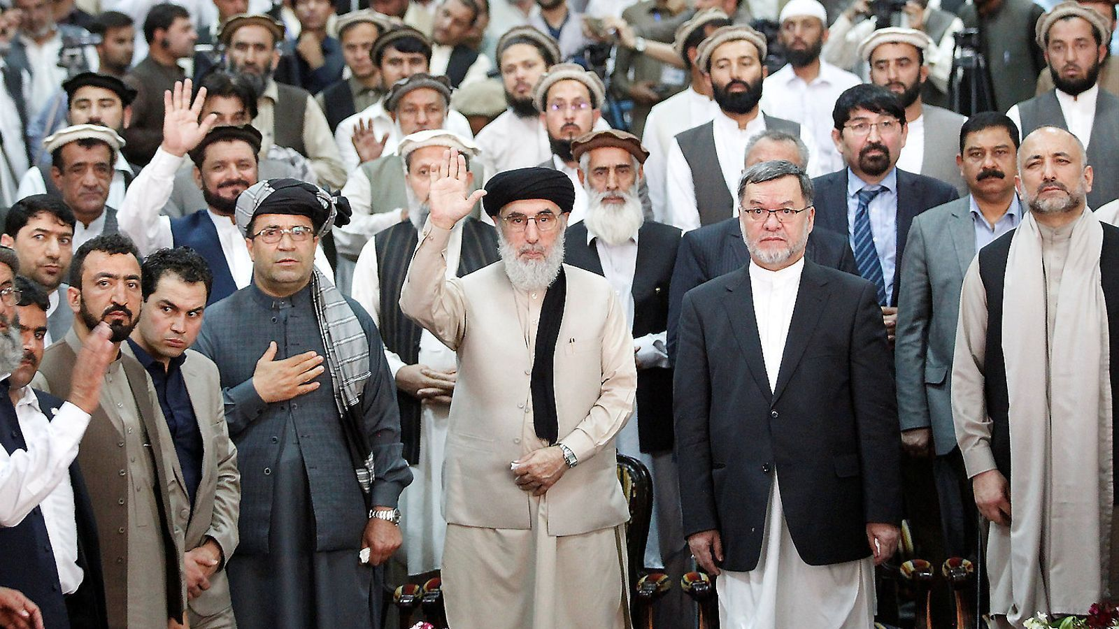 Gulbuddin Hekmatyar saludant amb la mà, al centre de la imatge.