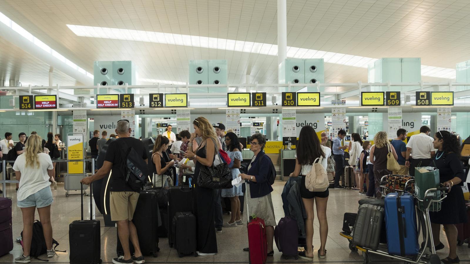 Cues als mostradors de Vueling ahir a l'aeroport del Prat.