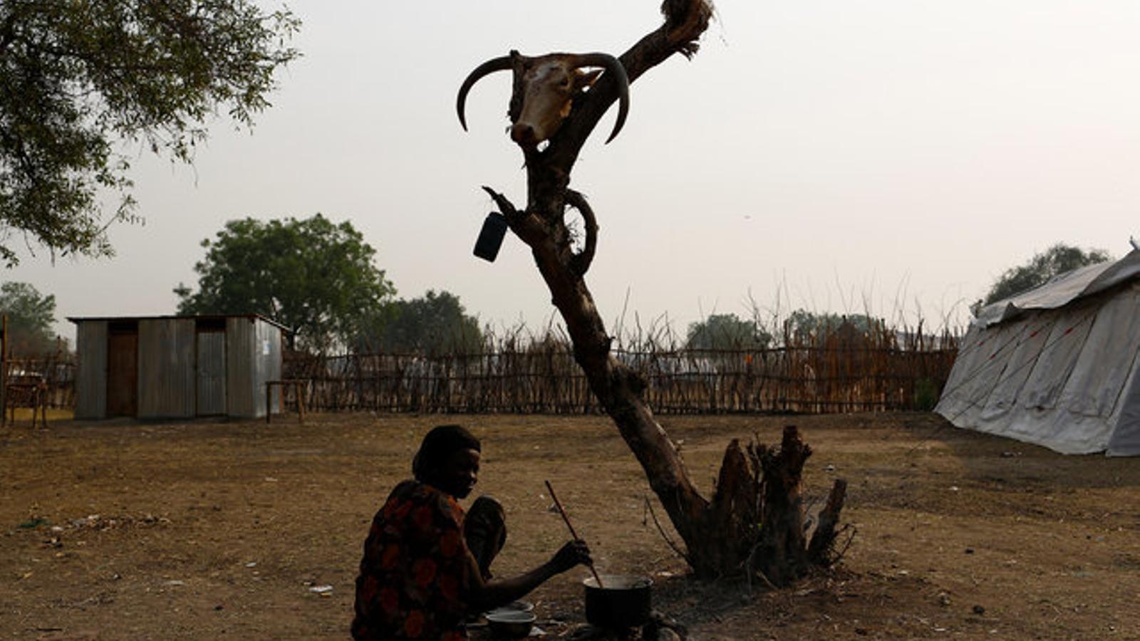 Una dona cuina al poblat de Pibor, a l'est del Sudan del Sud.