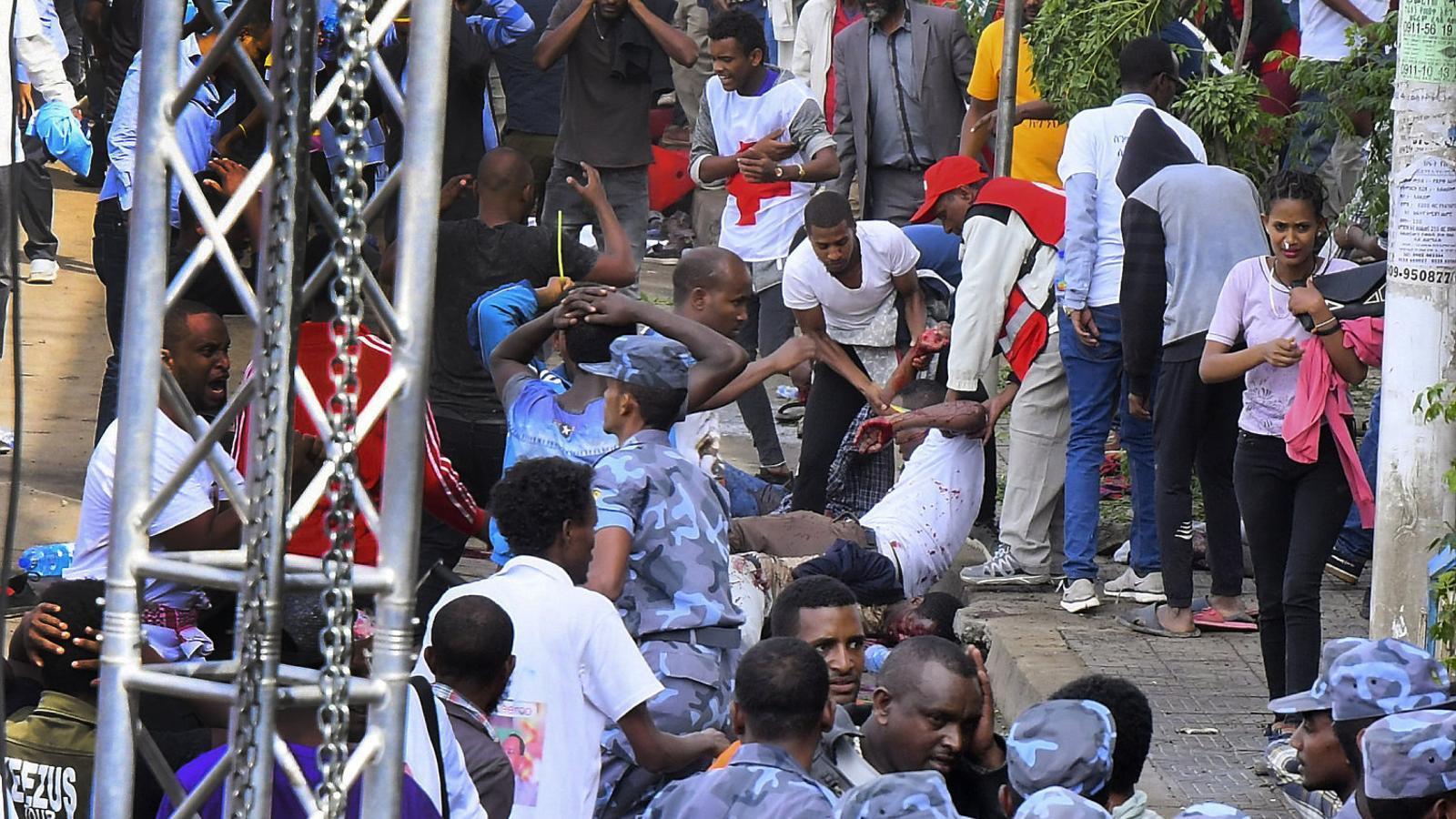 Diverses persones ajudant un ferit ahir en l'atac a Addis Abeba.