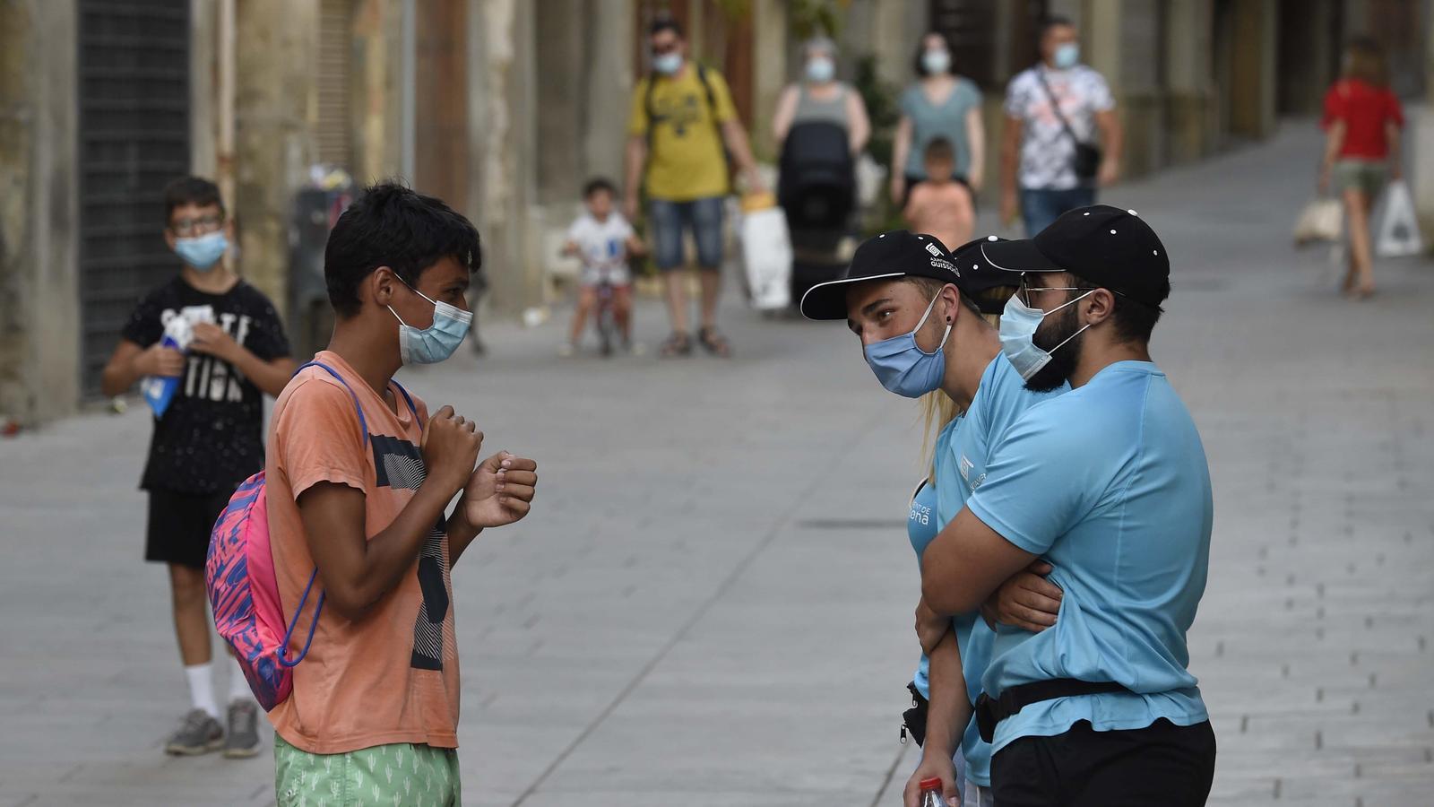 Un grup d'agents cívics de Guissona parlant amb un noi