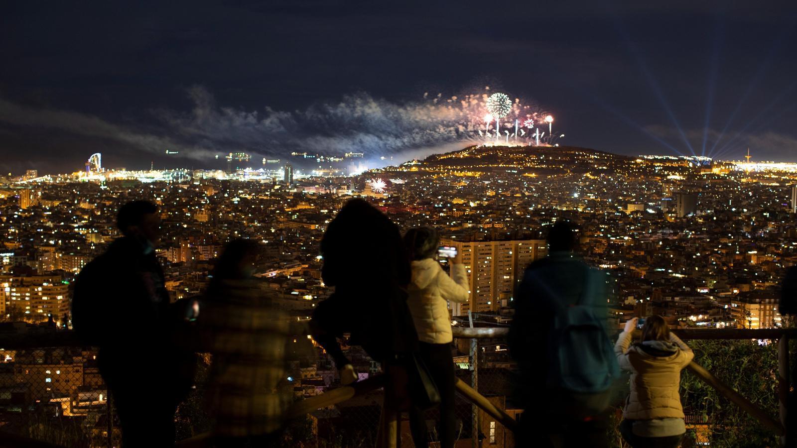Diverses persones observant els focs artificials de Cap d'Any a Barcelona