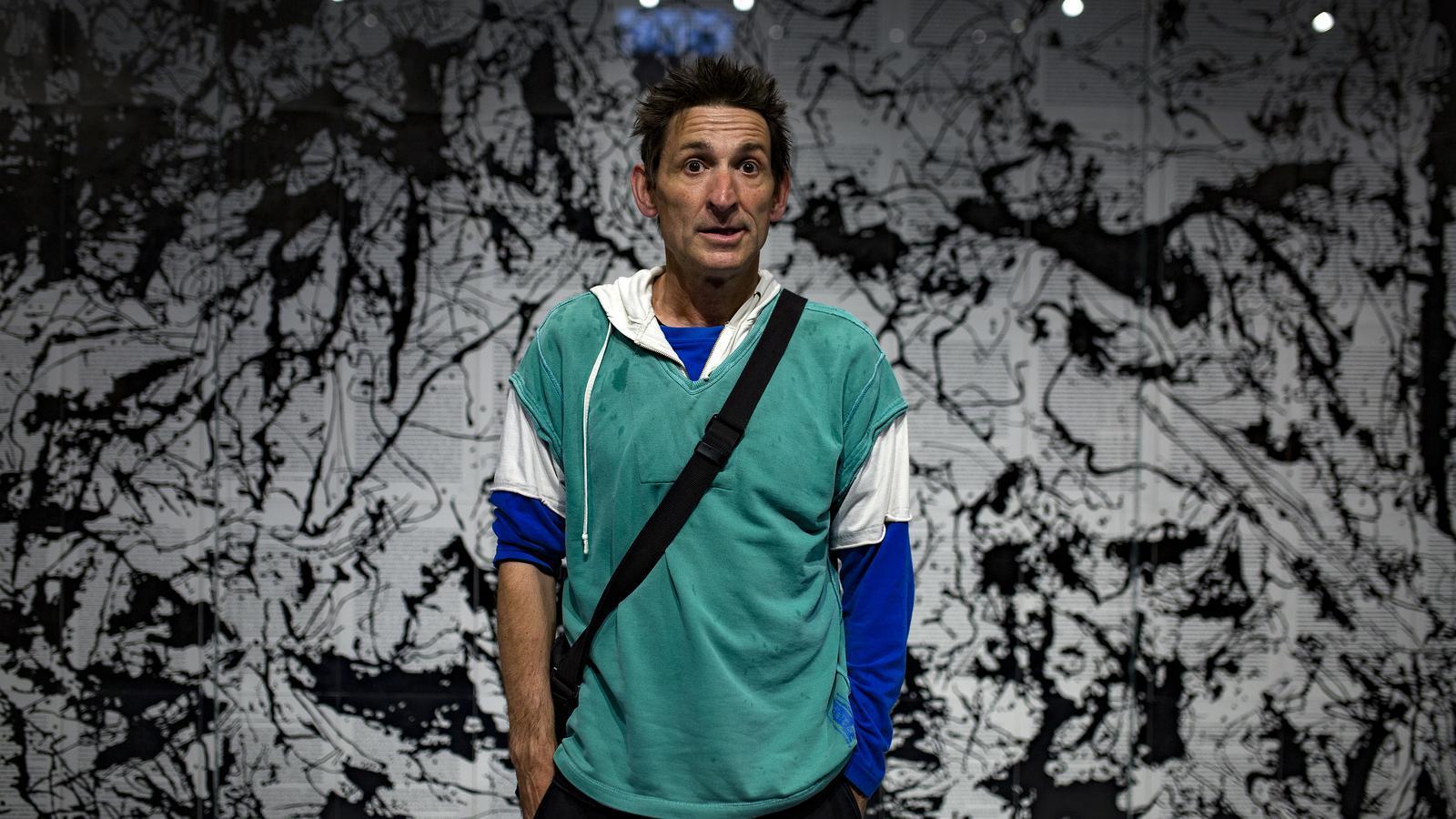 Albert Pla davant l'obra d'Art & Language 'Picasso's Guernica in the style of Jackson Pollock' a la llibreria Ona del carrer Pau Claris de Barcelona.