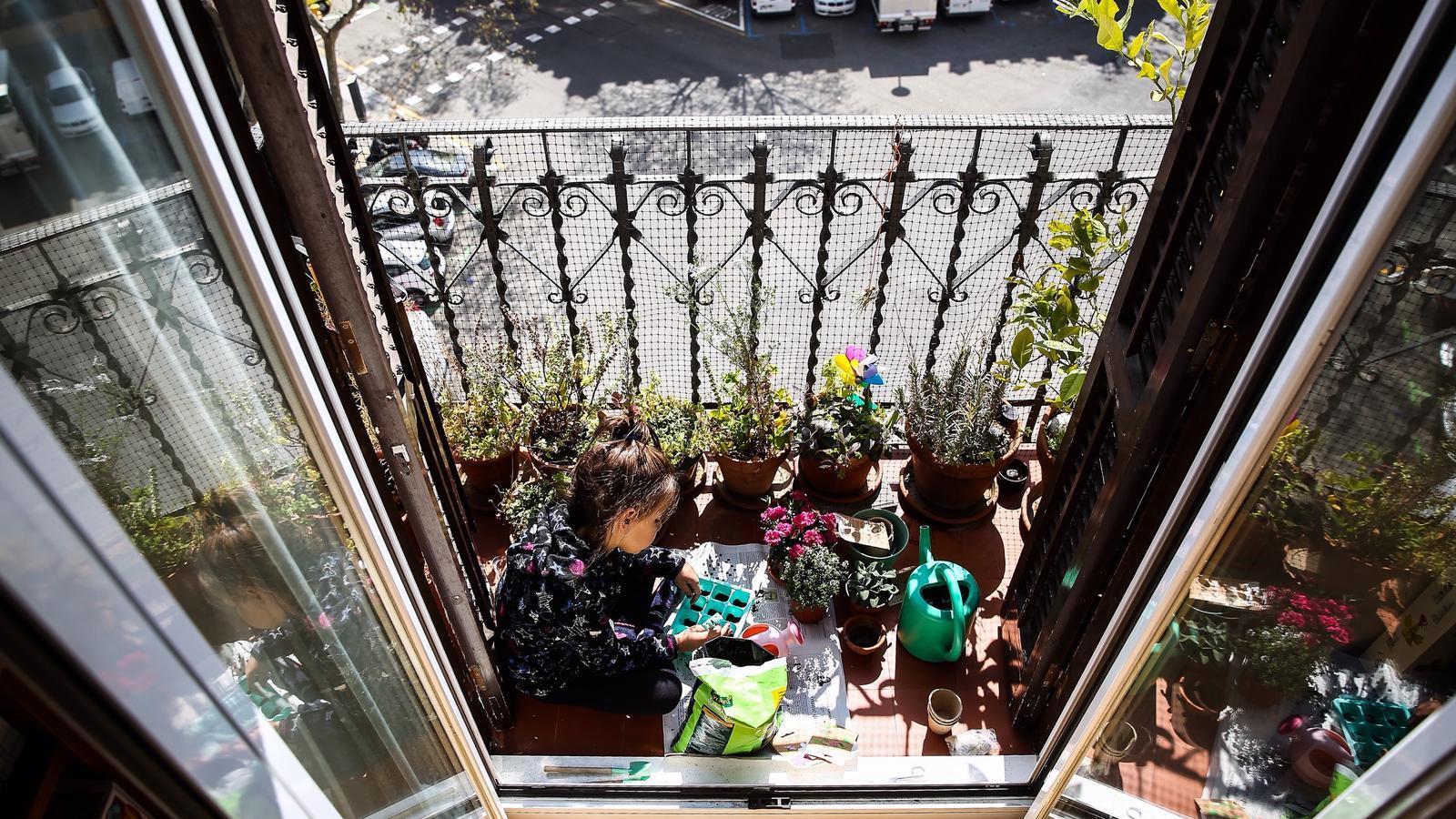Una nena jugant amb plantes al balcó