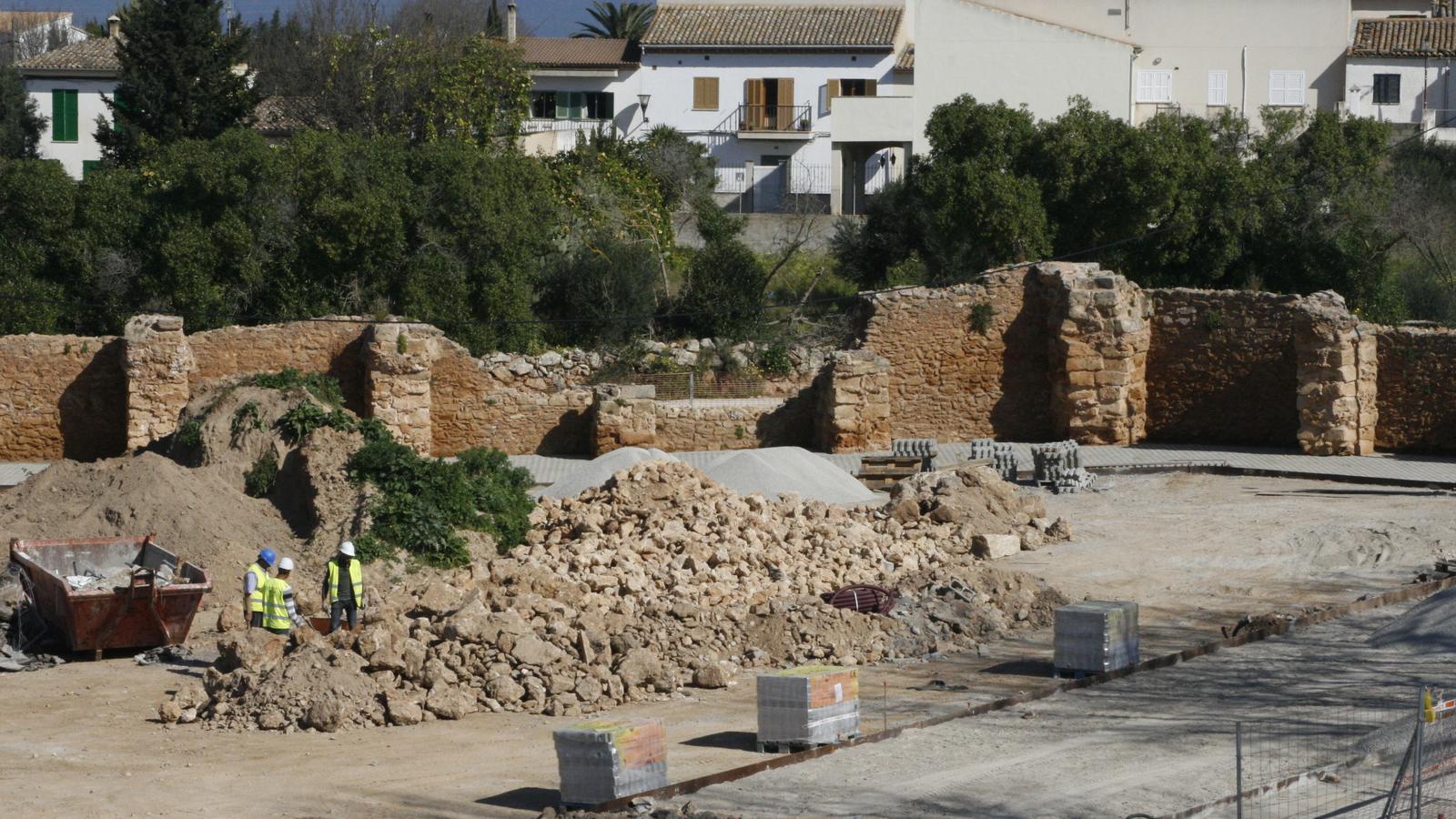 Operaris del sector de la construcció treballant en la restauració d'una de les murades.