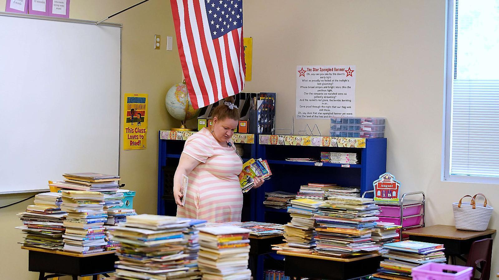 Una professora netejant i endreçant una aula d'una escola als Estats Units abans que es reprenguin les classes.